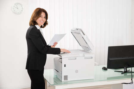 photocopy: Smiling Businesswoman Copying Paper On Photocopy Machine In Office