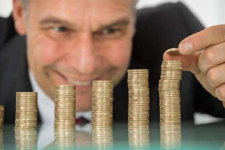 incremento: Feliz maduro hombre de negocios colocación de la moneda sobre la pila de monedas en el escritorio