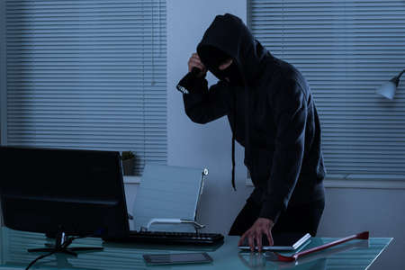 Robber Stealing Laptop With Flashlight In Hand Stock Photo