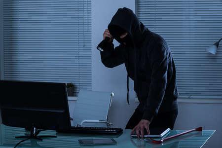 burglar: Robber Stealing Laptop With Flashlight In Hand Stock Photo