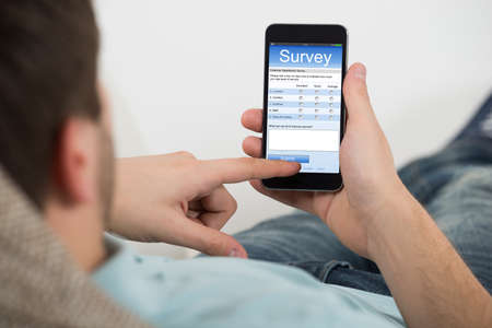 online survey: Close-up Of Young Man Filling Online Survey Form On Mobile Phone