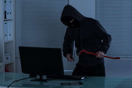 offense: Thief Stealing Laptop From Office At Night Stock Photo