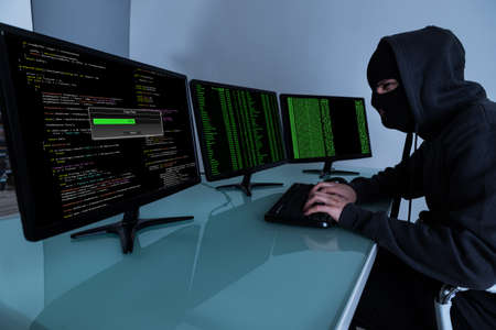 computer hacker: Hacker Stealing Data On Multiple Computers And Laptop