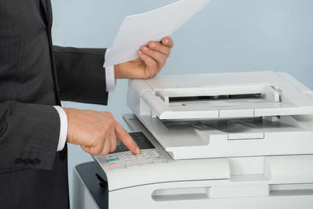 Close-up Of Businessman Hand Pressing Printer's Button In Office