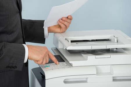fotocopiadora: Primer plano del hombre de negocios Mano presionando el botón de la impresora en oficina Foto de archivo