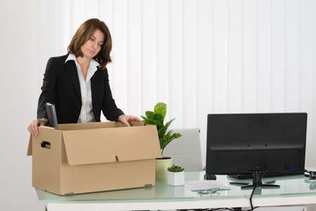 unemployed dismissed: Sad Young Businesswoman Packing Her Belongings In Box On Desk