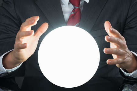 soothsayer: Close-up Of Businessman Hand On Crystal Ball On Desk Stock Photo