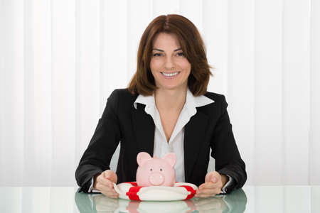 sheltering: Happy Young Businesswoman Sheltering Piggybank With Lifebelt