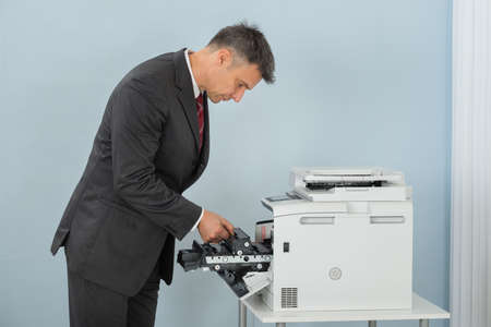 printer cartridge: Mature Businessman Fixing Cartridge In Printer Machine At Office Stock Photo