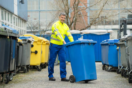 during the day: Happy Male Worker Walking With Dustbin On Street During Day Stock Photo