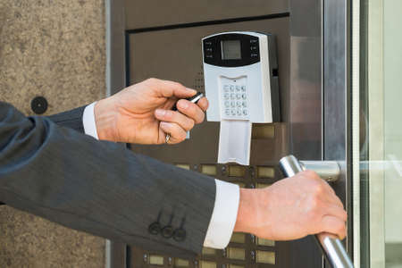 operating system: Close-up Of Businessperson Hand Using Remote Control For Operating Door In Security System
