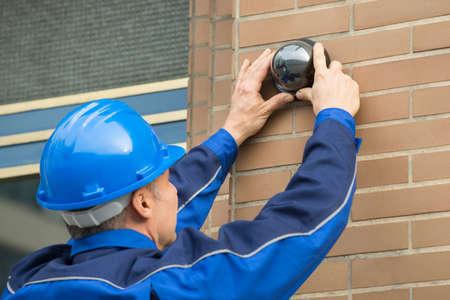 Close-up von einer reifen Mann Techniker Installieren von Camera In Building Lizenzfreie Bilder