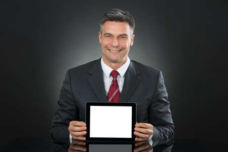 blank tablet: Mature Happy Businessman Showing Tablet With Blank Screen At Desk Stock Photo