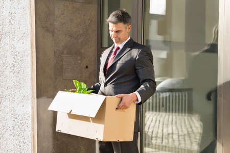 moving out: Sad Mature Businessman Moving Out With Cardboard Box From Office Stock Photo