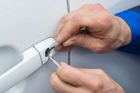 Primer De La Persona mano que sostiene el LockPicker para abrir la puerta del coche