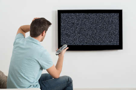 Man Sitting On Sofa In Front Of Television With No Signal Stock Photo