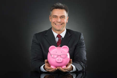smart investing: Mature Happy Businessman Sitting And Holding Piggybank Stock Photo