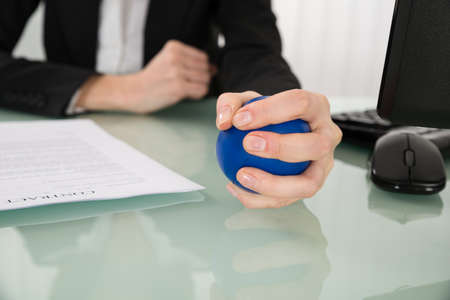 squeeze: Close-up Of Businesswoman Pressing Stressball In Office