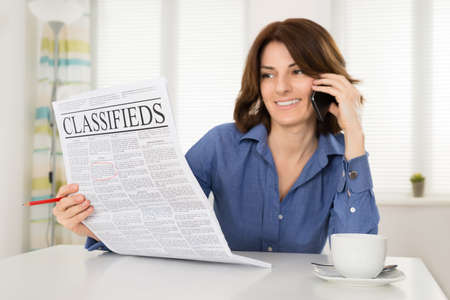 classified ad: Happy Young Woman Holding Newspaper While Talking On Mobile Phone In Office Stock Photo