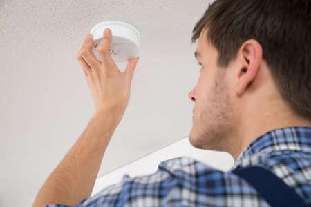 sensor: Male Electrician With Screwdriver Repairing Fire Sensor