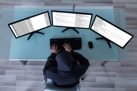 multiple: High Angle View Of Hacker Stealing Information From Multiple Computers