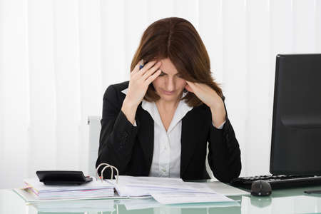 stressed people: Stressed Businesswoman Sitting In Office With Financial Report