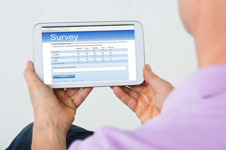 electronic voting: Man Holding Mobile Phone Showing Survey Form At Home Stock Photo
