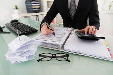事務所の税を計算するビジネスマンのクローズ アップ