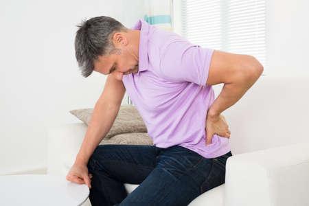 back injury: Mature Man Having Backache While Sitting On Sofa