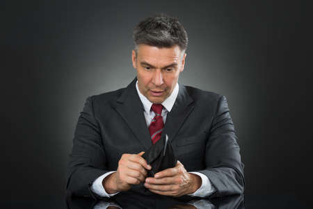 sitting at desk: Sad Businessman With Empty Wallet Sitting At Desk Against Gray Background