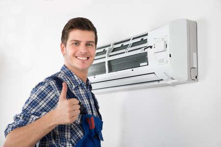 the maintenance: Hombre joven feliz Técnico gestos pulgar