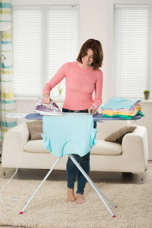 hold on: Happy Young Woman Ironing Clothes On Iron Board