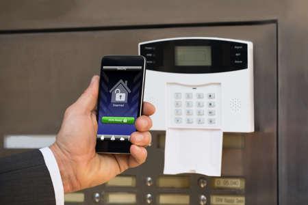 seguridad en el trabajo: Primer Del Empresario mano que sostiene el teléfono inteligente Para armar el sistema Foto de archivo