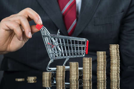 inflation basket: Close-up Of Businessman With Stack Of Coins And Small Shopping Cart At Desk