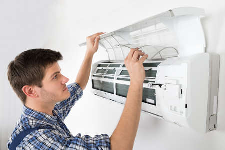 man in air: Young Male Technician Cleaning Air Conditioning System At Home