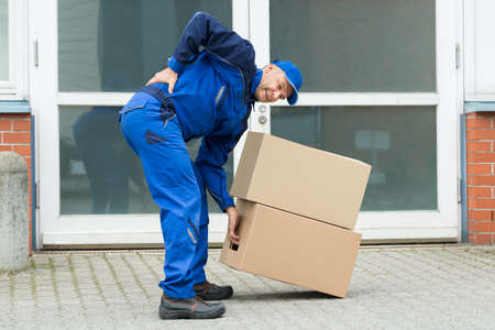 moving box: Delivery Man Suffering From Backpain While Lifting Boxes