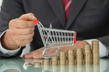inflation basket: Close-up Of Businessman Hand Holding Small Shopping Cart Placed Near Stack Of Coins At Desk Stock Photo