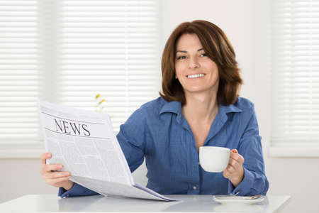 Young Happy Woman With Coffee Cup And Newspaper