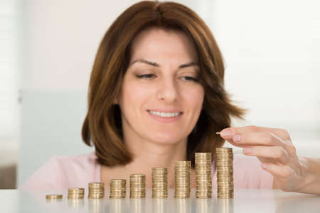 woman holding money: Young Happy Woman Stacking Coins At Desk Stock Photo