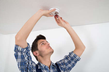 detector: Young Male Electrician Repairing Smoke Detector On Wall Stock Photo