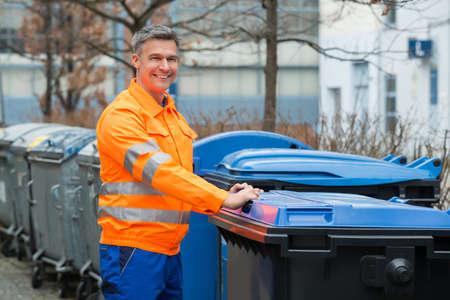 recolector de basura: Hombre de funcionamiento feliz cerca del cubo de basura de la calle Coloca En
