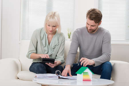ecosystems: Couple Calculating Tax With House Model Showing Energy Efficiency Rate On Desk Stock Photo
