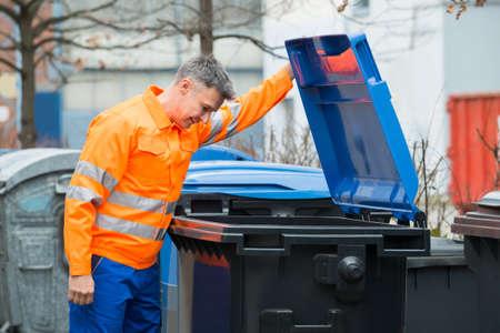 recolector de basura: Funcionamiento del hombre que mira en Cubo de basura en la calle Foto de archivo
