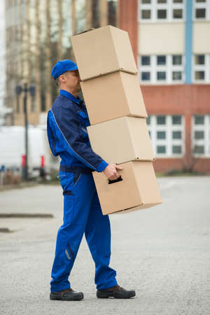 delivery box: Mature Delivery Man Balancing Stack Of Boxes Stock Photo