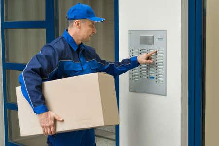 건물을 입력하려면 인터콤의 골 판지 상자를 누르면 버튼과 함께 배달 남자 스톡 콘텐츠