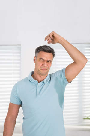 mans shirt: Man With Hyperhidrosis Sweating Very Badly Under Armpit At Home