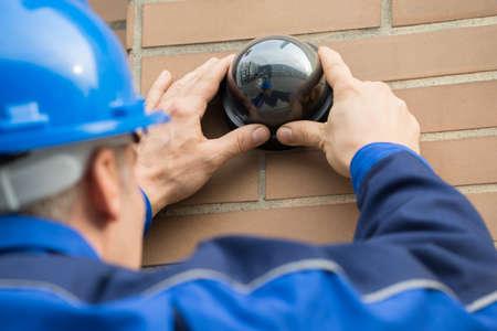 建物にカメラをインストールする成熟した男性技術者のクローズ アップ