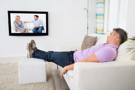 Mature Man Sleeping On Sofa While Watching Television At Home photo