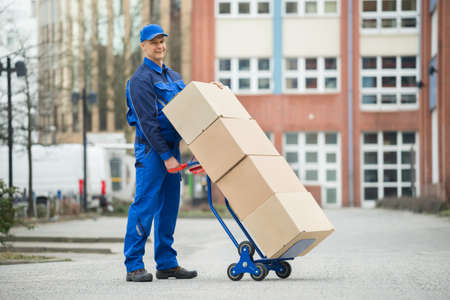 loaded: Mature Happy Deliveryman Holding Trolley Loaded With Cardboard Boxes On Street Stock Photo