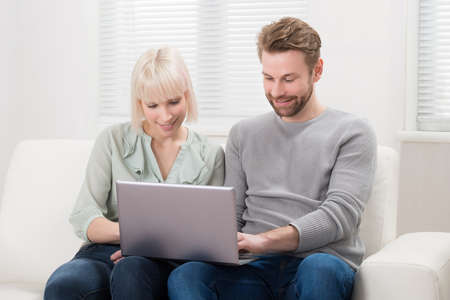 couple on couch: Happy Young Couple Sitting On Couch Using Laptop At Home